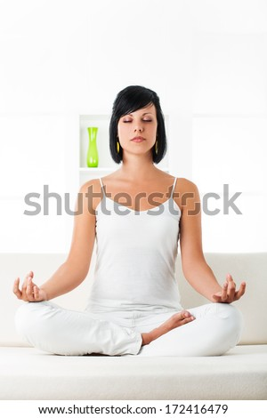 Fit young woman spending yoga time by herself in her living room - stock photo