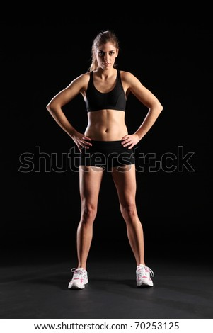 Fit young woman standing in black sports outfit - stock photo