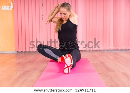 Fit Young Woman Stretching her Arms and Legs While Sitting on a Mat Inside a Fitness Studio. - stock photo