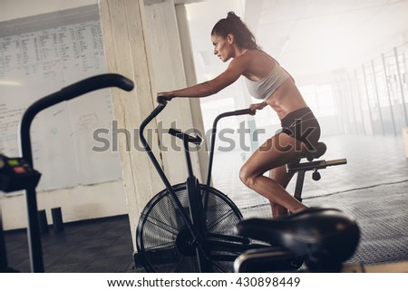 Fit young woman using exercise bike at the gym. Fitness female using air bike for cardio workout at crossfit gym. - stock photo