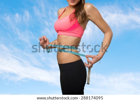 Fit young woman with a measurement scale. Over clouds background - stock photo
