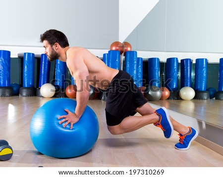 Fitball abdominal push ups Swiss ball man one single leg pushup at fitness gym - stock photo