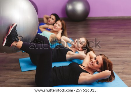 Fitball crunch training group core fitness at gym abdominal workout. fitness, sport, training and lifestyle concept - group of smiling women with exercise balls in gym - stock photo