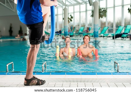 Fitness - a young couple - man and woman - doing sports and gymnastics or water aerobics under water in swimming pool or spa with swim noodle