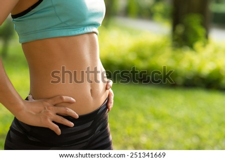 Fitness and diet concept: cropped image of woman in sportswear with perfect abs - stock photo