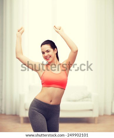 fitness and diet concept - smiling teenage girl in sportswear dancing - stock photo