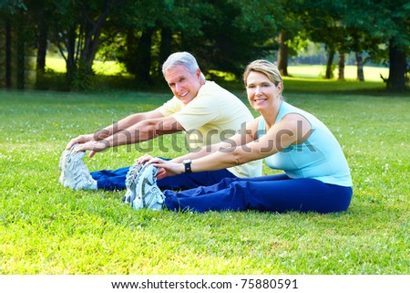 Fitness and healthy lifestyle. Senior couple doing exercise in the park. - stock photo