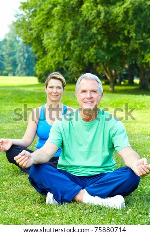 Fitness and healthy lifestyle. Senior couple doing yoga in the park. - stock photo