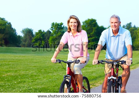 Fitness and healthy lifestyle. Senior couple riding in the park. - stock photo