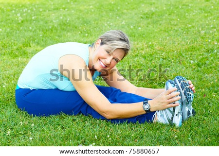 Fitness and healthy lifestyle. Senior woman doing exercise in the park. - stock photo