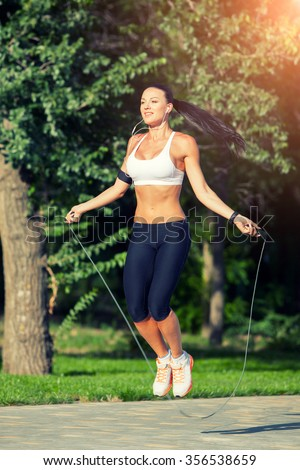fitness and lifestyle concept - woman doing sports outdoors. girl with skipping rope. - stock photo