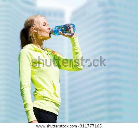 fitness and lifestyle concept - woman drinking water after doing sports outdoors - stock photo