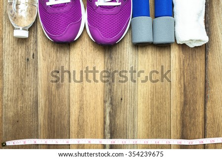 Fitness and sport equipment : Measuring tape,mat.sneakers,towel,bottle of water with wooden background on top view - stock photo