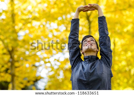 Fitness and stretching exercises outdoor. Beautiful sportswoman exercising on autumn park. Caucasian young sporty girl doing pilates. Copyspace. - stock photo