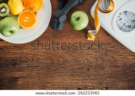 Fitness and weight loss concept, dumbbells, white scale, fruit and tape measure on a wooden table, top view - stock photo