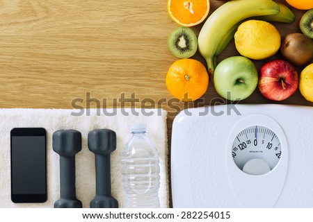 Fitness and weight loss concept, dumbbells, white scale, towel, fruit and mobile phone on a wooden table, top view - stock photo