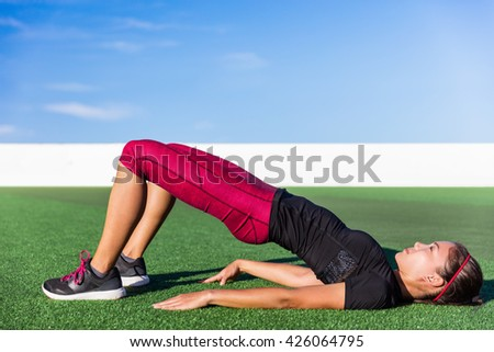 Fitness Asian woman doing bodyweight glute exercises with floor bridge hip raise butt life leg exercise outdoor grass gym. Healthy lifestyle strength training workout in activewear. - stock photo
