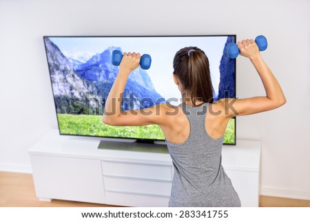Fitness at home - woman working out in front of tv. Back of a young female adult watching television during her workout, lifting weights to tone arms and shoulders, following an exercise video. - stock photo