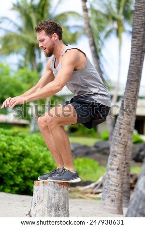 Fitness athlete bench jump squat jumping outside in nature landscape. Strength training fit male working out exercising outdoors on beach in summer doing jumping on tree trunk. - stock photo