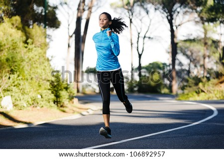 Fitness athlete training alone on a mountain road. Running endurance marathon woman exercising for healthy lifestyle and wellness.