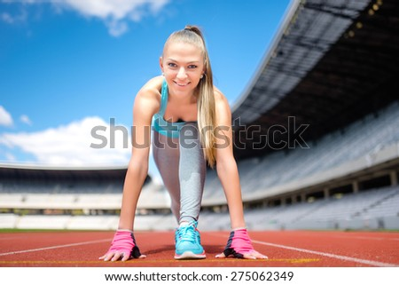 Fitness athletic girl preparing for a run on sport track at stadium.  Healthy and sporty lifestyle with young girl running - stock photo