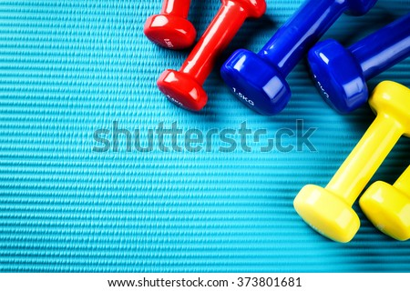 Fitness background with colorful dumbbells. Healthy lifestyle concept with copy space