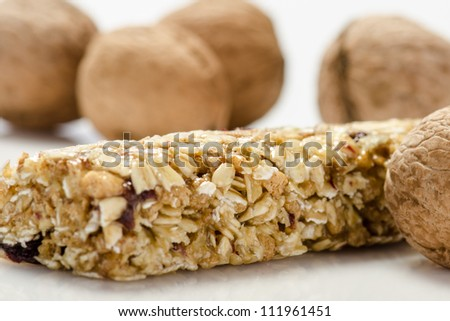 Fitness bar  and nuts against white background - stock photo