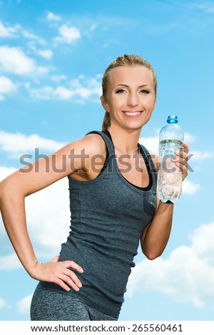 Fitness beautiful blonde woman drinking  water after sports on the background of sky and clouds - stock photo