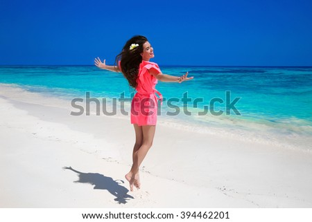 Fitness. Beautiful happy woman jumping on exotic sea, brunette smiling girl in red dress enjoying on tropical beach. Enjoyment. Lifestyle. Freedom. Good life. Travel.  - stock photo