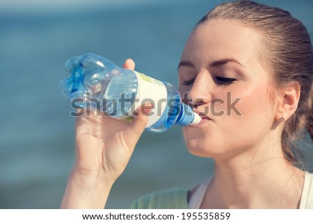 Fitness beautiful woman drinking water and sweating after exercising on summer hot day in beach