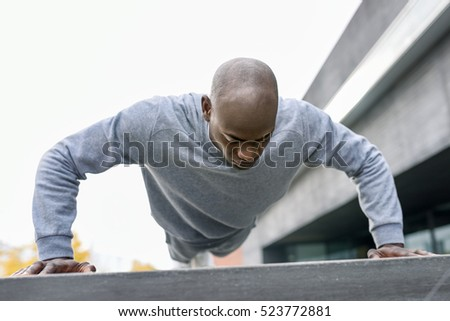 Fitness black man exercising push ups. Male model cross-training in urban background  African guy in his twenties doing workout outdoors in the street.