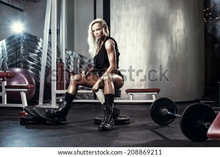 fitness blonde sexy girl posing on bench in the gym in military style clothes
