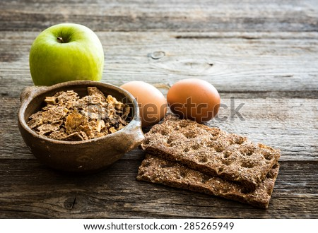 fitness breakfast with eggs, flakes, grey bread and green apple on wooden background - stock photo