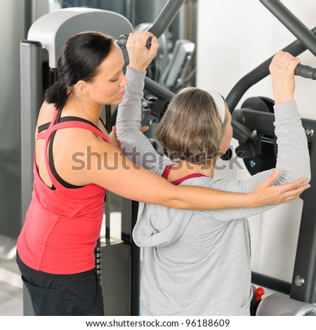 Fitness center personal trainer senior woman exercise shoulder on machine