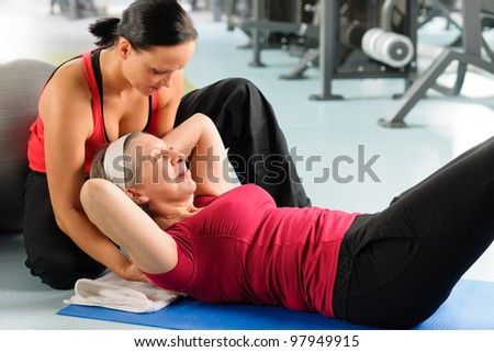 Fitness center senior woman exercise with personal trainer on mat - stock photo