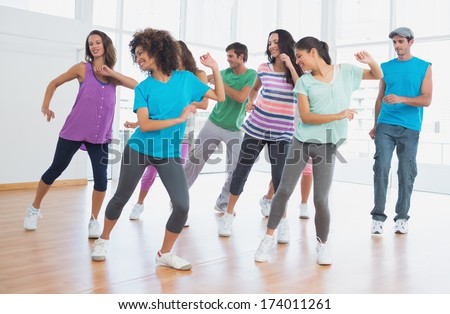 Fitness class and instructor doing pilates exercise in a bright room - stock photo