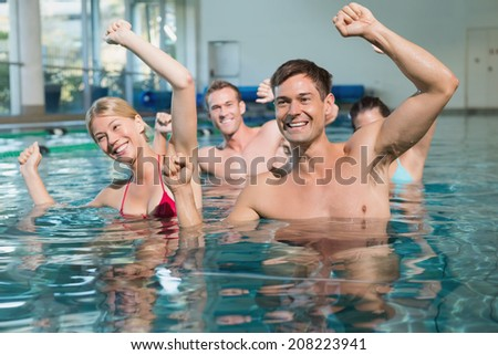 Fitness class doing aqua aerobics in swimming pool at the leisure centre - stock photo