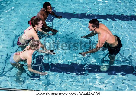 Fitness class doing aqua aerobics on exercise bikes in swimming pool - stock photo