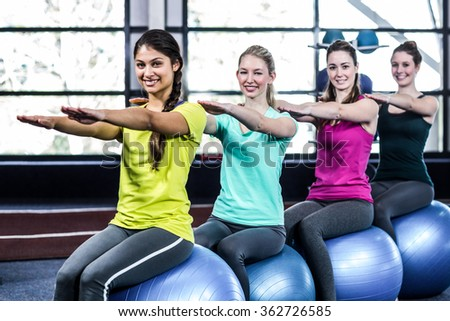 Fitness class doing sit ups on exercise balls in gym - stock photo