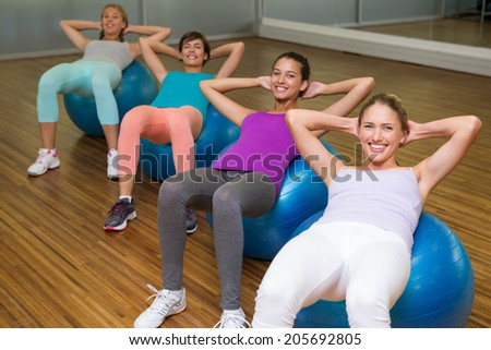 Fitness class doing sit ups on exercise balls in studio at the gym - stock photo