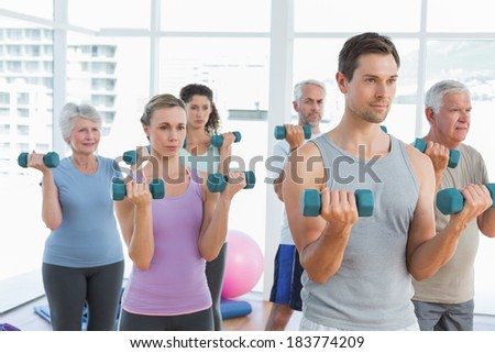 Fitness class exercising with dumbbells in a bright gym - stock photo
