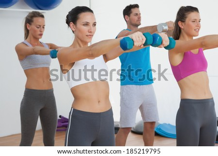Fitness class exercising with dumbbells in the gym - stock photo