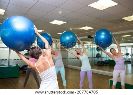 Fitness class holding up exercise balls in studio at the gym - stock photo