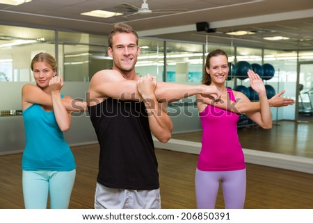 Fitness class led by handsome instructor at the gym - stock photo