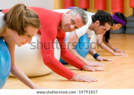 Fitness class lying on front on fitness balls at gym, mature instructor in the centre - stock photo