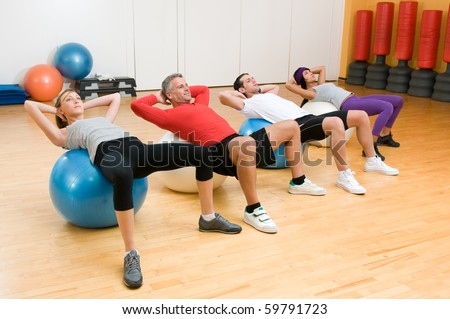 Fitness class making sit-ups on fitness ball at gym, mature instructor in the centre - stock photo