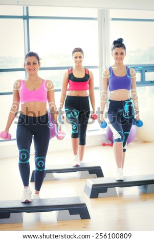 Fitness class performing step aerobics exercise with dumbbells against fitness interface - stock photo