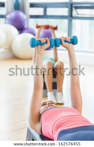 Fitness class performing step aerobics exercise with dumbbells in a gym - stock photo