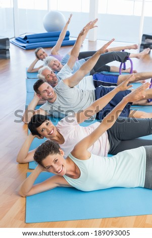 Fitness class stretching legs and hands in row at yoga class - stock photo