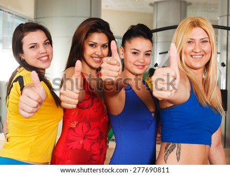 Fitness class women showing thumbs up - stock photo